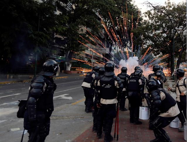 Bolivarian National Police officers take cover from exploding fireworks launched at them by anti-government demonstrators during clashes in Caracas, Venezuela, Thursday, March 6, 2014. A National Guardsman and a civilian were killed Thursday in a clash between residents of a Caracas neighborhood and armed men who tried to remove a barricade, Venezuelan officials said. (AP Photo/Fernando Llano)