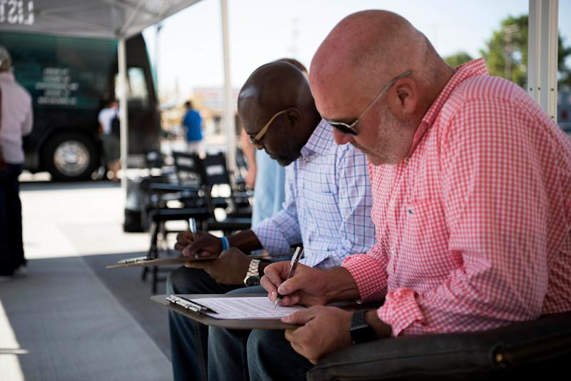 Reggie Davis, left, and Andy Nix sign up to go on the HuffPost bus.