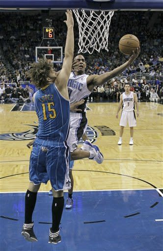Orlando Magic's Arron Afflalo, right, takes a shot as New Orleans Hornets' Robin Lopez (15) defends during the first half of an NBA basketball game on Wednesday, Dec. 26, 2012, in Orlando, Fla. (AP Photo/John Raoux)