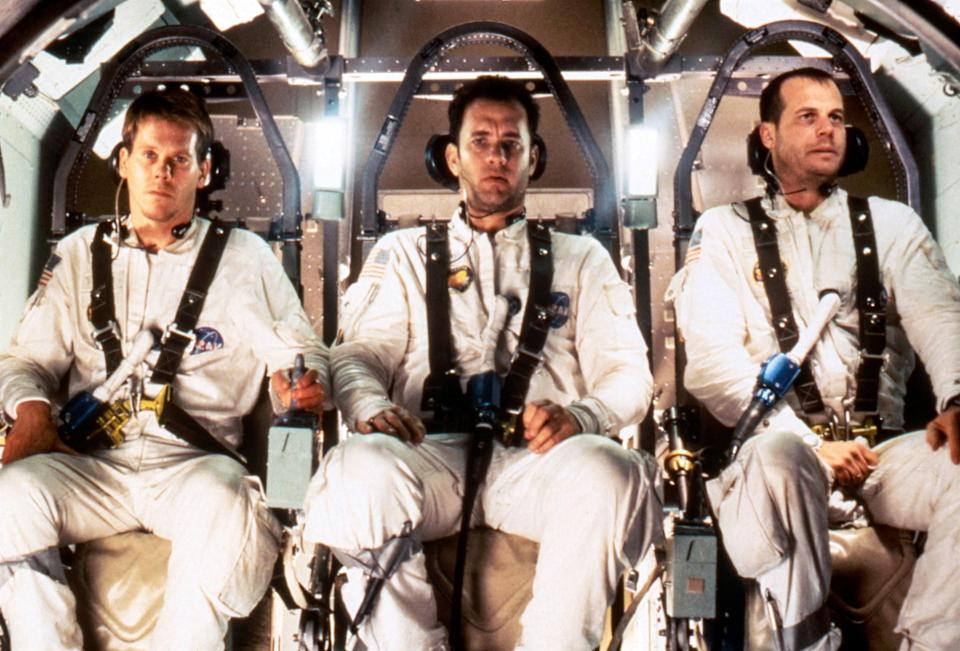 Fred Haise, Jack Swigert, and Jim Lovell wearing their NASA uniforms in the space shuttle in the film