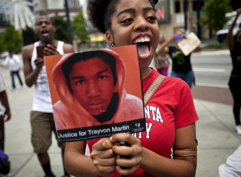 Averri Liggins, 22, of Atlanta, chants while holding a picture of Trayvon Martin during a protest the day after George Zimmerman was found not guilty in the 2012 shooting death of Martin, Sunday, July 14, 2013, in Atlanta. From New York to California, outrage over the acquittal of George Zimmerman poured from street demonstrations and church pulpits Sunday. (AP Photo/David Goldman)