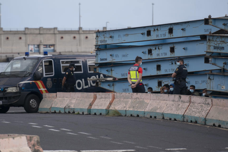 Police officers detain migrants who tried to reach the Spanish Peninsula by ferry, in Santa Cruz de Tenerife, Spain, Sunday, March 21, 2021. While Spain has been critical of its European neighbours' lack of solidarity when it comes to sharing the responsibility of migration, the country is similarly being criticized by migrants, authorities and human rights organizations on the Canary Islands where some 23,000 people arrived by sea last year and where many thousands remain on the island forcefully. (AP Photo/Joan Mateu)