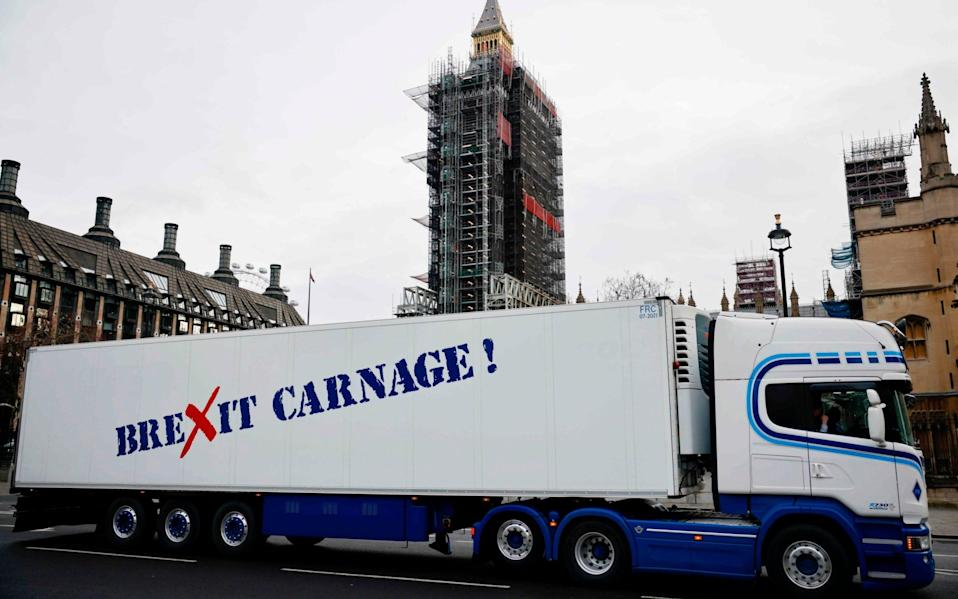 """A truck drives past the Houses of Parliament with a message that reads """"Brexit carnage!"""" in a protest action by Scottish fishermen against post-Brexit red tape - AFP"""