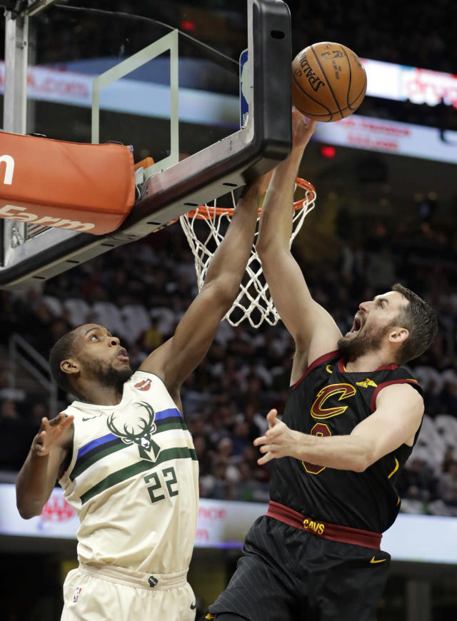 Milwaukee Bucks' Khris Middleton (22) blocks a shot by Cleveland Cavaliers' Kevin Love (0) in the first half of an NBA basketball game, Monday, March 19, 2018, in Cleveland. (AP Photo/Tony Dejak)