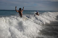 """U.S. tourist Latron Evans and his partner Nika, frolicking ocean waters at the beach in Tulum, Quintana Roo state, Mexico, Monday, Jan. 4, 2021. Evans, a Mississippi firefighter, said he was impressed by the health measures due to the new coronavirus pandemic. """"They're taking temperatures when you enter the building and giving you hand sanitizer every place you go, it's required. It's not that way in the states,"""" he said. (AP Photo/Emilio Espejel)"""