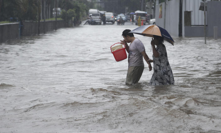 Indonesian people wade through floodwaters in Jakarta, Indonesia, Monday, Feb. 9, 2015. Seasonal rains and high tides in recent days have caused widespread flooding across much of Indonesia. (AP Photo/Achmad Ibrahim)