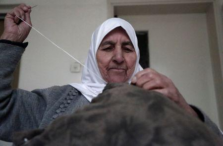 Ezzeya Daraghmeh, an 82-year-old Palestinian woman who said she has kept parts of her hair she cut over 67 years, sews a pillow that she stuffed with her hair, in the West Bank town of Tubas January 2, 2018. Picture taken January 2, 2018. REUTERS/Raneen Sawafta