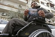 In Damascus, 33-year-old Samer Sawwan holds a picture of himself before a bullet shot through his car in 2011, sending it into a roll that paralysed him forever