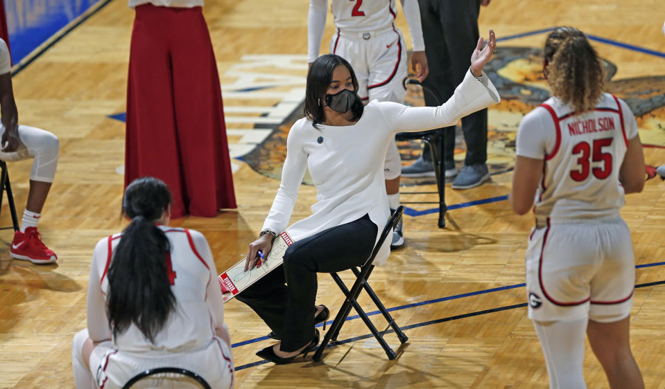 Georgia head coach Joni Taylor holds her meeting respecting social distancing during the first half of a college basketball game in the first round of the women's NCAA tournament at the Greehey Arena in San Antonio, Texas, Monday, March 22, 2021. (AP Photo/Ronald Cortes)