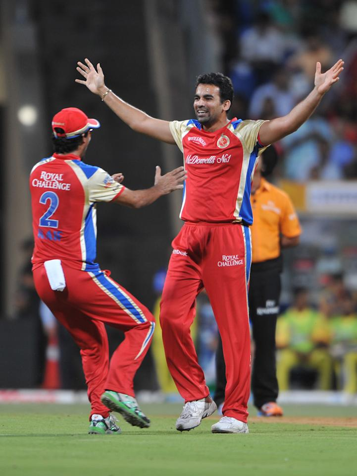 RESTRICTED TO EDITORIAL USE. MOBILE USE WITHIN NEWS PACKAGE   Royal Challengers Bangalore bowler Zaheer Khan (R) celebrates with his team mate after he dismissed Chennai Super Kings batsman Michael Hussey during the qualifier 1 match of IPL Twenty20 match between Chennai Super Kings and Royal Challengers Bangalore at The Wankhede Stadium in Mumbai on May 24, 2011. AFP PHOTO / Sajjad HUSSAIN (Photo credit should read SAJJAD HUSSAIN/AFP/Getty Images)