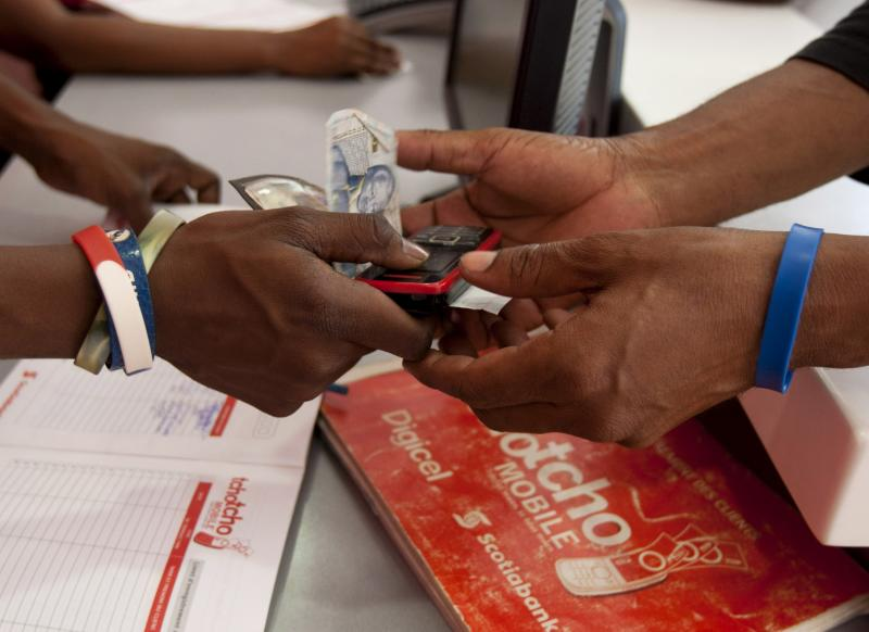 """In this June 4, 2012 photo, a man takes his money, along with his cell phone, at Digicel's """"TchoTcho Mobile"""" office in Port-au-Prince, Haiti. Aid agencies trying to remake Haiti after a catastrophic earthquake are promoting a new way to bypass banks altogether: easy money transfers by cell phone. The plan lets people save and move money in mobile phone accounts and quickly withdraw it at a network of retail stores around the country. (AP Photo/Dieu Nalio Chery)"""