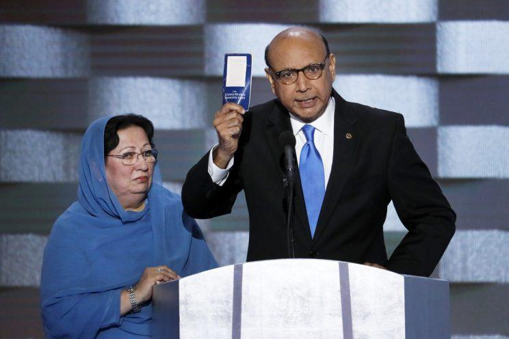 Khizr Khan, father of fallen U.S. Army Capt. Humayun Khan, holds up a copy of the Constitution as his wife listens at the Democratic convention. (J. Scott Applewhite/AP)