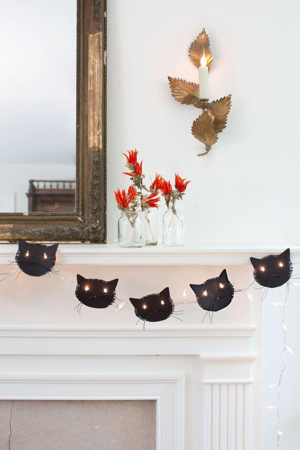 """<p>For Halloween, delight your kids with <em>purrfect</em> cat garland that's made with string lights. </p><p><a href=""""https://www.countryliving.com/home-design/decorating-ideas/g1936/halloween-mantel-ideas/?slide=15"""" rel=""""nofollow noopener"""" target=""""_blank"""" data-ylk=""""slk:Get the tutorial here >>"""" class=""""link rapid-noclick-resp""""><em>Get the tutorial here >></em></a></p>"""