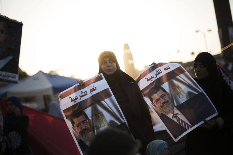 """A woman supporter of Egypt's ousted President Mohammed Morsi holds a banner of the former president with Arabic that reads """"yes to legitimacy,"""" during a protest near Cairo University in Giza, Egypt, Thursday, August, 1, 2013. Authorities offered """"safe passage and protection"""" Thursday for thousands of supporters of ousted President Mohammed Morsi if they end their two large sit-ins in Cairo. The Interior Ministry's offer appears to be the first step by Egypt's new leadership to clear away the Morsi supporters from where they have been camped since shortly before he was toppled by the army July 3. (AP Photo/Manu Brabo)"""