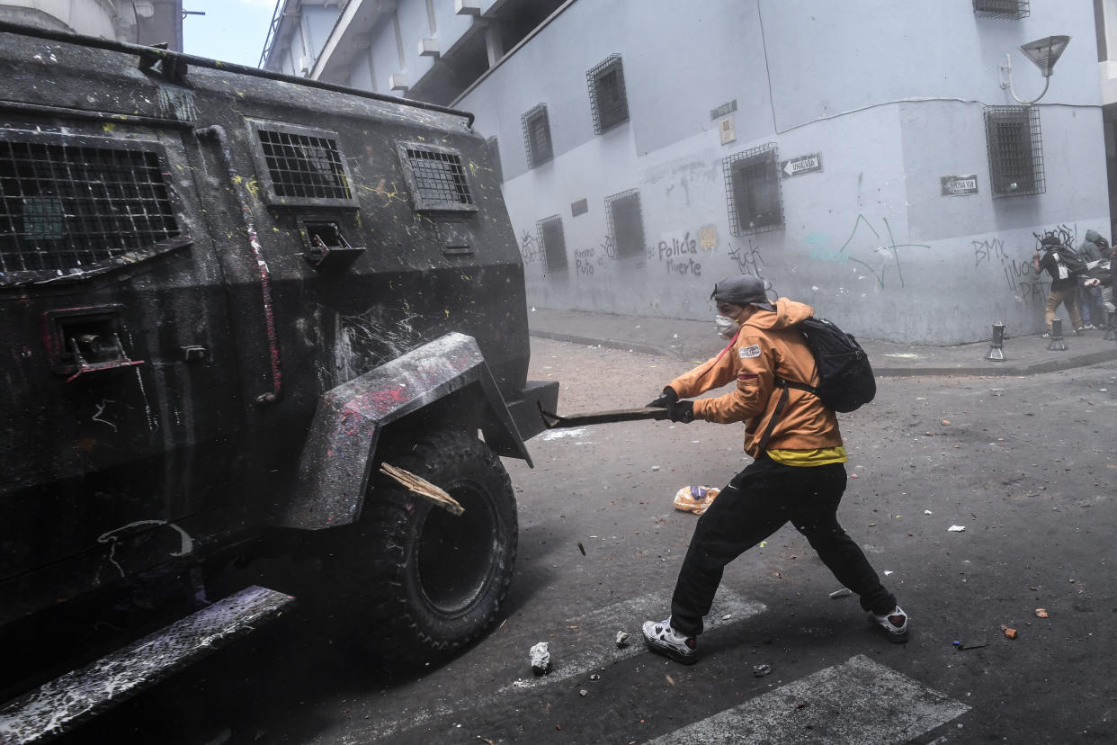 A demonstrator hits a riot police vehicle with a stick during clashes in Quito, as thousands march against Ecuadorean President Lenin Moreno's decision to slash fuel subsidies, on Oct. 9, 2019. (Photo: Martin Bernetti/AFP via Getty Images)
