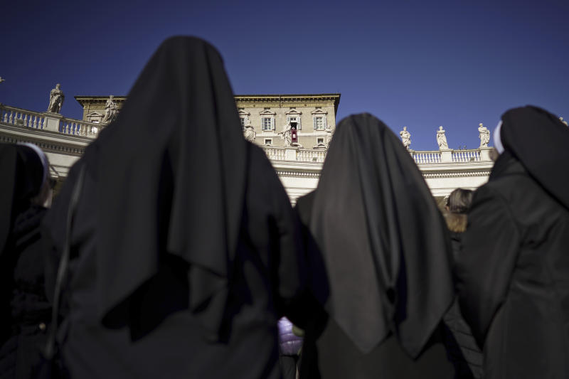 Nuns watch Pope Francis as he delivers his blessing during the Angelus noon prayer he recited from the window of his studio overlooking St. Peter's Square, at the Vatican, Thursday, Dec. 26, 2019. (AP Photo/Andrew Medichini)