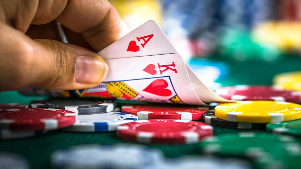 Gambling Hand Holding Poker Cards and Money Coins Chips.