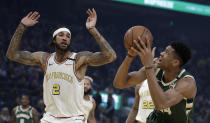 Milwaukee Bucks' Giannis Antetokounmpo, right, shoots as Golden State Warriors' Willie Cauley-Stein (2) defends during the first half of an NBA basketball game Wednesday, Jan. 8, 2020, in San Francisco. (AP Photo/Ben Margot)