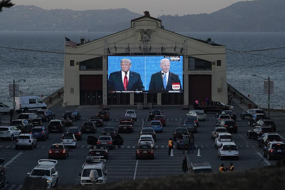 Cars parked in front of a large outdoor video screen showing the debate