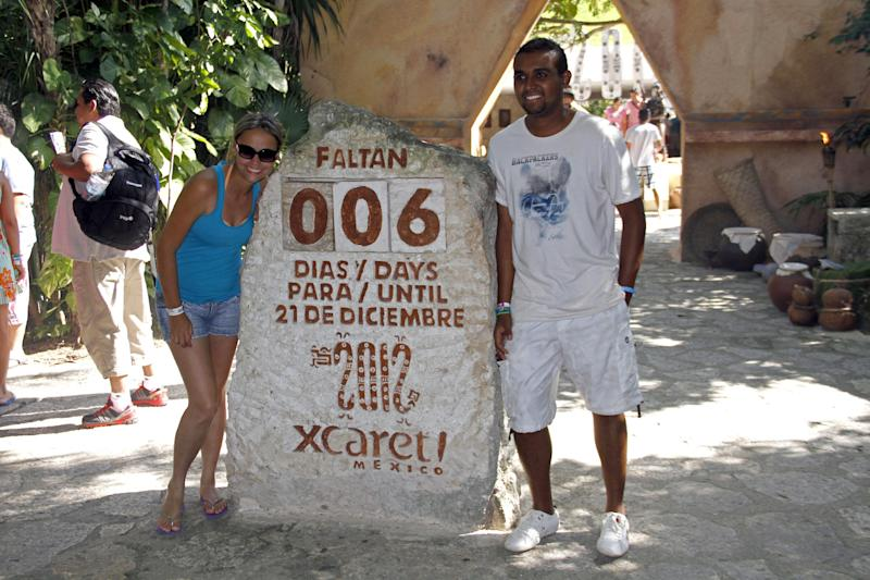 Tourists get their picture taken next to a slab of stone counting down the days until Dec. 21, 2012 at the Xcaret theme park in Playa del Carmen, Mexico, Saturday, Dec. 15, 2012. Amid a worldwide frenzy of advertisers and new-agers preparing for a Maya apocalypse, one group is approaching Dec. 21 with calm and equanimity calm: the people whose ancestors supposedly made the prediction in the first place. Mexico's 800,000 Mayas are not the sinister, secretive, apocalypse-obsessed race they've been made out to be.  (AP Photo/Israel Leal)