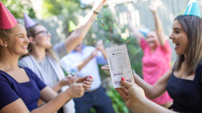 Stock image of a woman holding a winning OZ Lotto ticket in front of group of friends.
