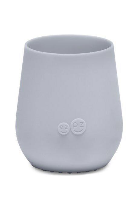 """<p><strong>ezpz</strong></p><p>bedbathandbeyond.com</p><p><strong>$9.99</strong></p><p><a href=""""https://www.bedbathandbeyond.com/store/product/ezpz-tiny-cup/5306709"""" target=""""_blank"""">Shop Now</a></p><p>Drinking from an open cup is an important milestone for babies six months and older because it helps with oral and speech development. This mini cup is<strong> </strong>made to fit baby hands and gives a good grip thanks to the food-grade silicone (bonus: it's chewy for when they're teething). There's also a <strong>textured, weighted base to prevent tipping</strong> and it's dishwasher safe so it's easy to clean. Even better, it's only 10 bucks and it comes in lots of colors. The brand also makes matching <a href=""""https://www.bedbathandbeyond.com/store/product/ezpz-tiny-spoons-set-of-2/5306810"""" target=""""_blank"""">tiny spoons</a> to help with self-feeding skills.</p>"""