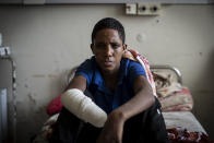 """Haftom Gebretsadik, a 17-year-old from Freweini, Ethiopia, near Hawzen, who had his right hand amputated and lost fingers on his left after an artillery round struck his home in March, sits on his bed at the Ayder Referral Hospital in Mekele, in the Tigray region of northern Ethiopia, on Thursday, May 6, 2021. """"I am very worried,"""" he said. """"How can I work?"""" As the Tigray People's Liberation Front and the government forces fight, civilians are suffering heavily. (AP Photo/Ben Curtis)"""