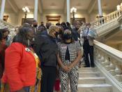 """FILE - In this Friday, Feb. 26, 2021 file photo, Georgia House Democrats speak with Democratic Rep. Park Cannon, right, in Atlanta during a sit-in at the state capitol sparked by opposition to Republican proposals that would restrict voting. On Friday, March 5, 2021, The Associated Press reported on a video circulating online incorrectly asserting left-wing protesters stormed Georgia's Capitol building in Atlanta or engaged in an insurrection over a bill that would require photo ID for absentee voting. However, the Georgia Department of Public Safety confirmed to the AP that the protesters entered the state Capitol lawfully and remained peaceful, unlike the rioters in the violent Jan. 6 insurrection in Washington. """"No one was arrested,"""" spokesperson Franka Young wrote. (AP Photo/Jeff Amy)"""