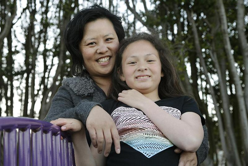 Joyce Chen hugs her daughter Kathryn, 10, as they pose for photographs in San Francisco, Wednesday, May 29, 2013. A new poll finds that one in five unmarried women would consider having a child on their own, and more than a third would consider adopting solo, just one indication of America's changing family structures. (AP Photo/Jeff Chiu)