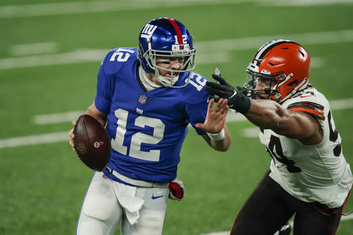 New York Giants quarterback Colt McCoy (12) evades Cleveland Browns' Olivier Vernon (54) during the first half of an NFL football game, Sunday, Dec. 20, 2020, in East Rutherford, N.J. (AP Photo/Seth Wenig)