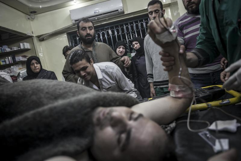 In this Saturday, Oct. 27, 2012 photo, Syrian civilian sob as a relative lies on a hospital trolley after was wounded with a sniper shot to his back, in the Aleppo, Syria. (AP Photo/Narciso Contreras).