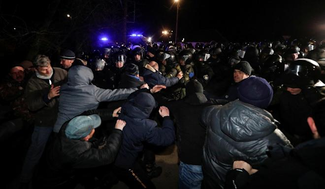 Ukrainian law enforcement officers clear the way as demonstrators block a road during a protest against the arrival of a plane carrying evacuees from China's Hubei province. Photo: Reuters