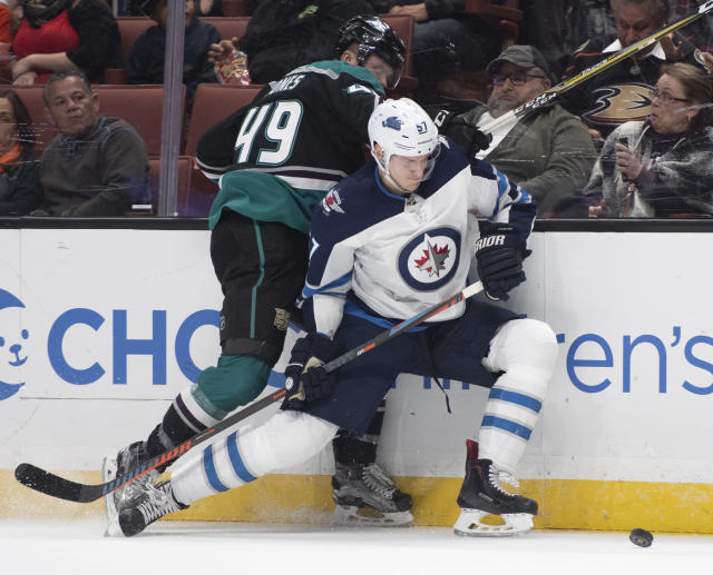 Winnipeg Jets defenseman Tyler Myers, right, and Anaheim Ducks left wing Max Jones compete for the puck during the second period of an NHL hockey game in Anaheim, Calif., Wednesday, March 20, 2019. (AP Photo/Kyusung Gong)