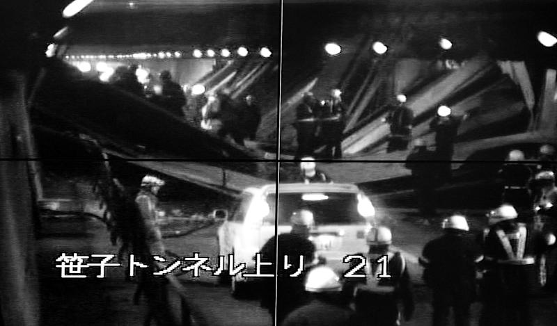 This image taken from the monitoring camera of Central Nippon Expressway's Hachioji branch, Tokyo, shows the rescuers looking for the injured among fallen roof panels in the Sasago Tunnel, Yamanashi Prefecture, central Japan, Sunday, Dec. 2, 2012.  At least seven people were feared missing after parts of the tunnel collapsed Sunday on the highway west of Tokyo, trapping vehicles as smoke from a fire inside initially prevented rescuers from approaching.  The words at bottom read: Sasago Tunnel (To Tokyo).  (AP Photo/Kyodo News) JAPAN OUT, MANDATORY CREDIT, NO LICENSING IN CHINA, FRANCE, HONG KONG, JAPAN AND SOUTH KOREA