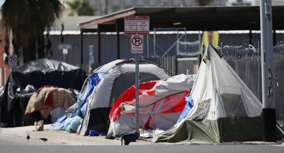Tents and crude lean-tos crowd the sidewalks where many homeless people live along the streets in record numbers, as concerns grow over the homeless population due to the coronavirus Tuesday, March 24, 2020, in Phoenix. (AP Photo/Ross D. Franklin)