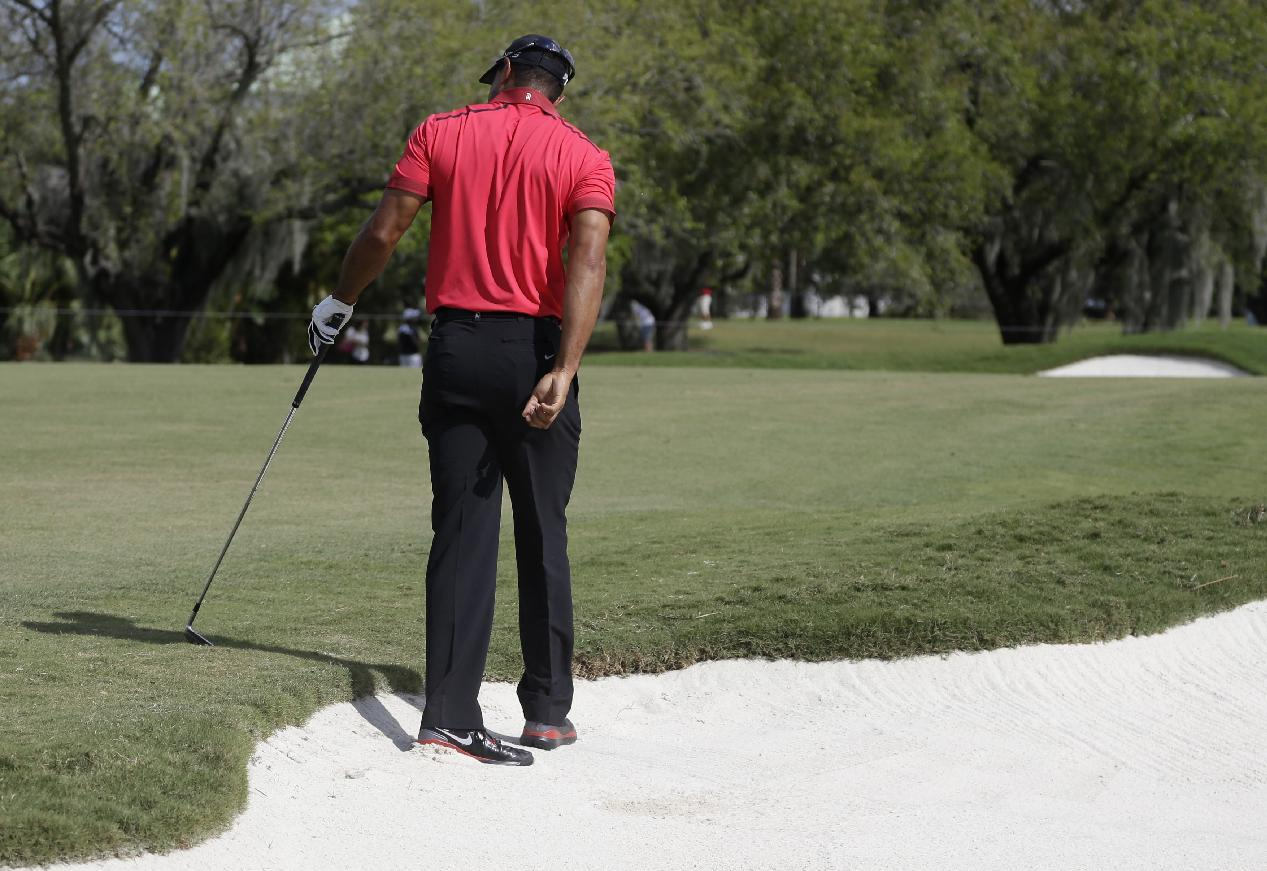 Tiger Woods turns his back after hitting from a bunker on the sixth hole during the final round of the Cadillac Championship golf tournament Sunday, March 9, 2014, in Doral, Fla. Woods' back flared up as a result of this shot. He would up with a 78, his highest score ever on Sunday, and for the first time fialed to make a single birdie in the final round. (AP Photo/Lynne Sladky)