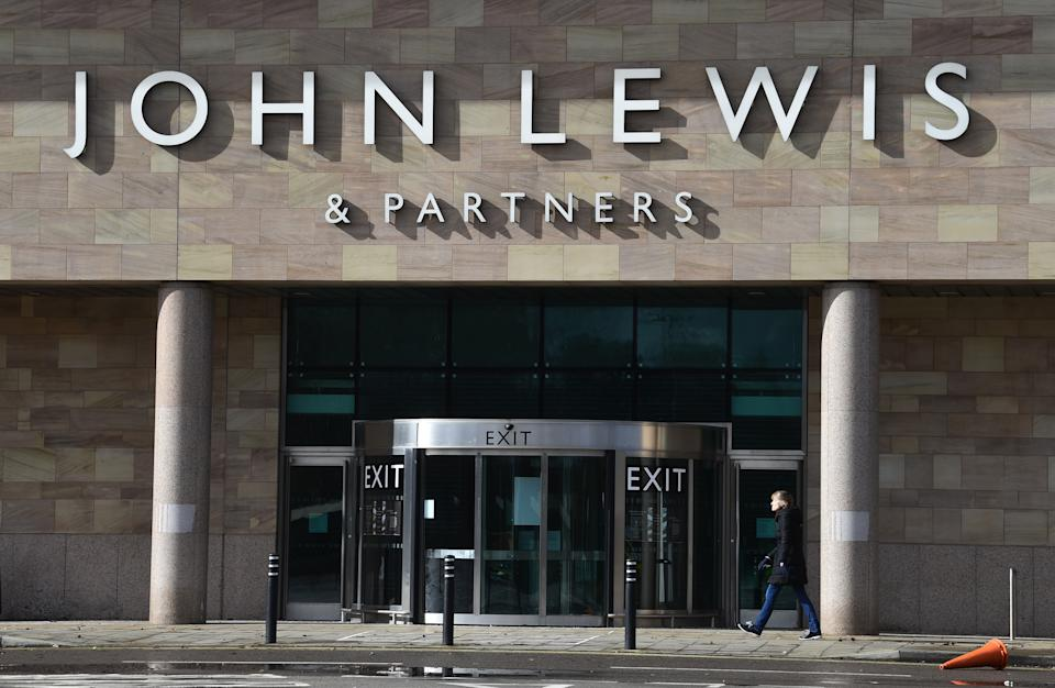 CHEADLE, ENGLAND- MARCH 12: A lady walks past a closed John Lewis department store on March 12, 2021 in Cheadle, England. (Photo by Nathan Stirk/Getty Images)
