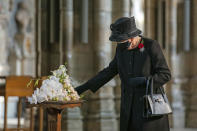 Britain's Queen Elizabeth II inspects a bouquet of flowers to be placed at the grave of the Unknown Warrior by her Equerry, Lieutenant Colonel Nana Kofi Twumasi-Ankrah, in Westminster Abbey, London, Wednesday, Nov. 4, 2020. Queen Elizabeth II donned a face mask in public for the first time during the coronavirus pandemic when attending a brief ceremony at Westminster Abbey last week to mark the centenary of the burial of the Unknown Warrior. While the 94-year-old has been seen in public on several occasions over the past few months, she has not worn a face covering. (Aaron Chown/Pool Photo via AP)
