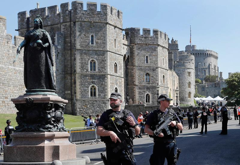 Armed British police officers hold their weapons as they secure teh procession route outside of Windsor Castle ahead of the wedding and carriage procession of Britain's Prince Harry, Duke of Sussex and Meghan Markle in Windsor, on May 19, 2018. (Photo by Frank Augstein / AFP) (Photo credit should read FRANK AUGSTEIN/AFP via Getty Images)