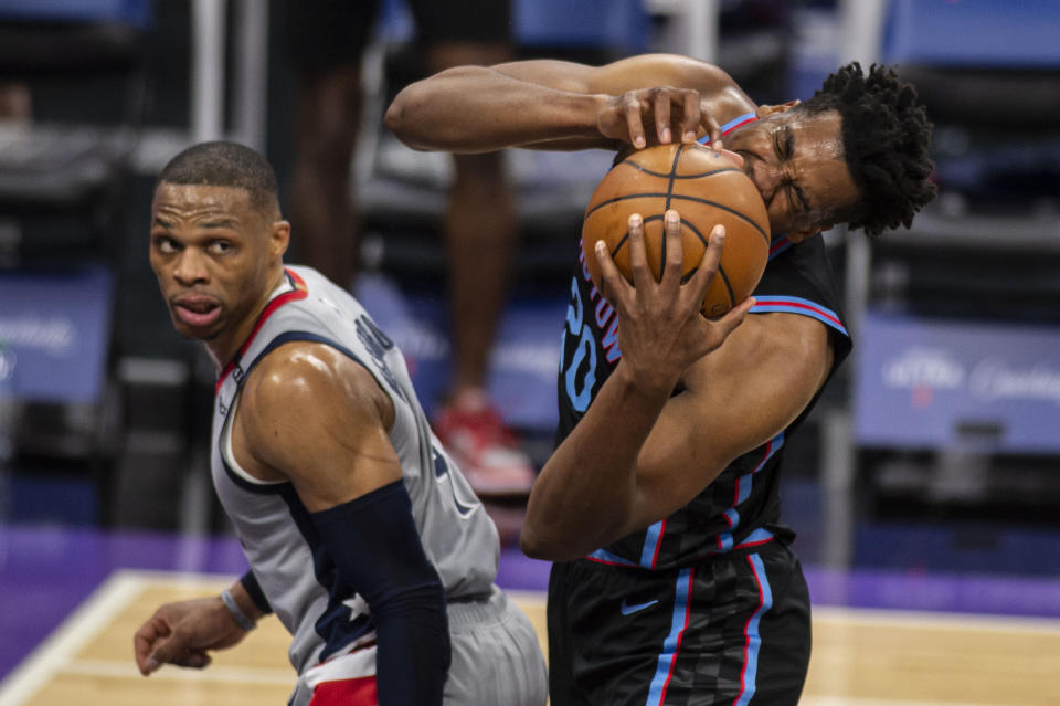 Sacramento Kings center Hassan Whiteside (20) reacts after getting fouled by Washington Wizards guard Russell Westbrook (4) during the second quarter of an NBA basketball game in Sacramento, Calif., Wednesday, April 14, 2021. (AP Photo/Hector Amezcua)