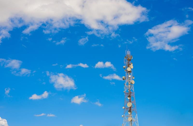 A densely populated cell tower set against blue skies and scattered clouds.