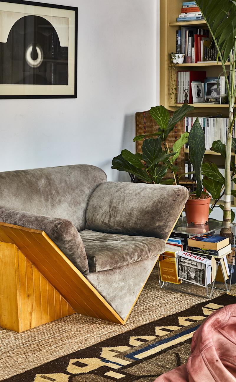 """A triangular wood-framed sofa and matching armchairs anchor the apartment's central sitting area. """"I wasn't sure about them at first,"""" Cyndia says. """"But the more I looked, the more interesting they became to me."""""""