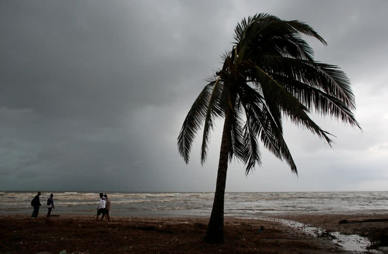 Residents walk along a beach after the passing of Hurricane Iota, in Puerto Cabezas