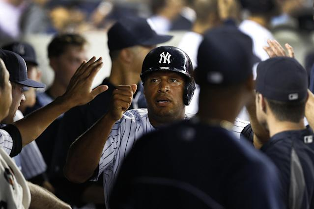 New York Yankees' Vernon Wells, center, celebrates with teammates in the dugout after stealing home in the second inning of a baseball game against the Chicago White Sox at Yankee Stadium, Tuesday, Sept. 3, 2013, in New York. (AP Photo/John Minchillo)