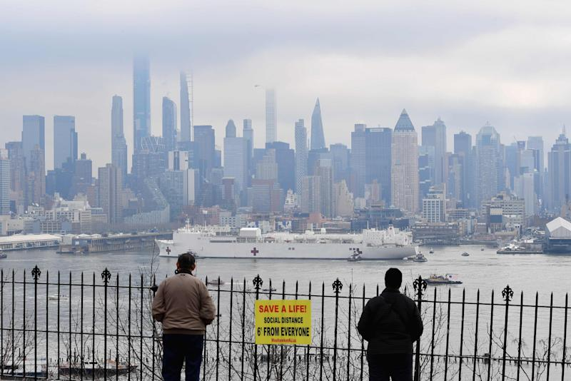 People watch as the USNS Comfort medical ship moves up the Hudson River as it arrives on March 30, 2020 in New York as seen from Weehawken, New Jersey.