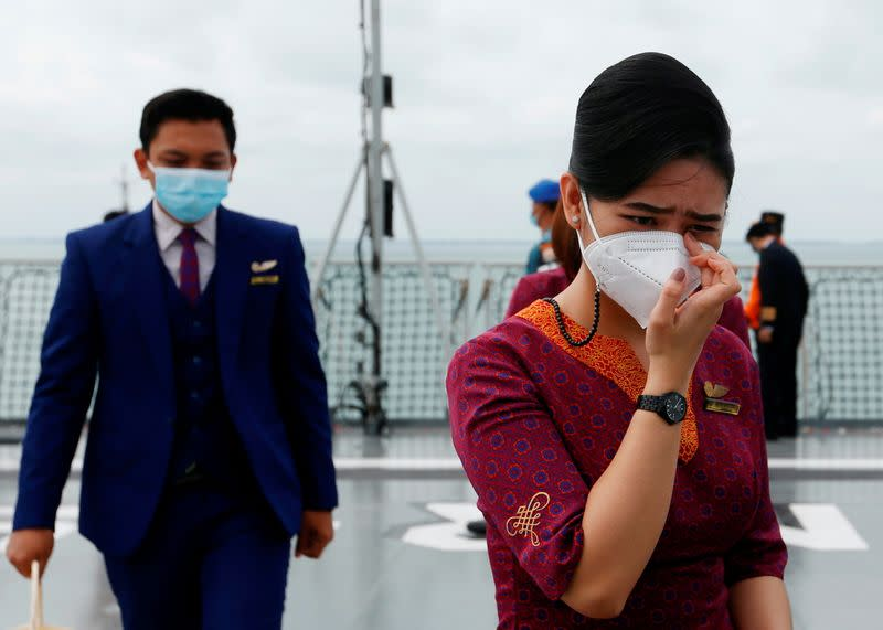 Flight attendants of Sriwijaya Air react as they visit the site of the crash of Sriwijaya Air flight SJ 182 to pay their tribute, on the deck of Indonesia's Naval ship KRI Semarang at the sea off the Jakarta coast