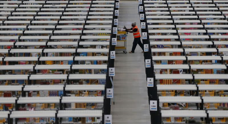 FILE PHOTO: A worker collects orders at Amazon's fulfilment centre in Rugeley, central England