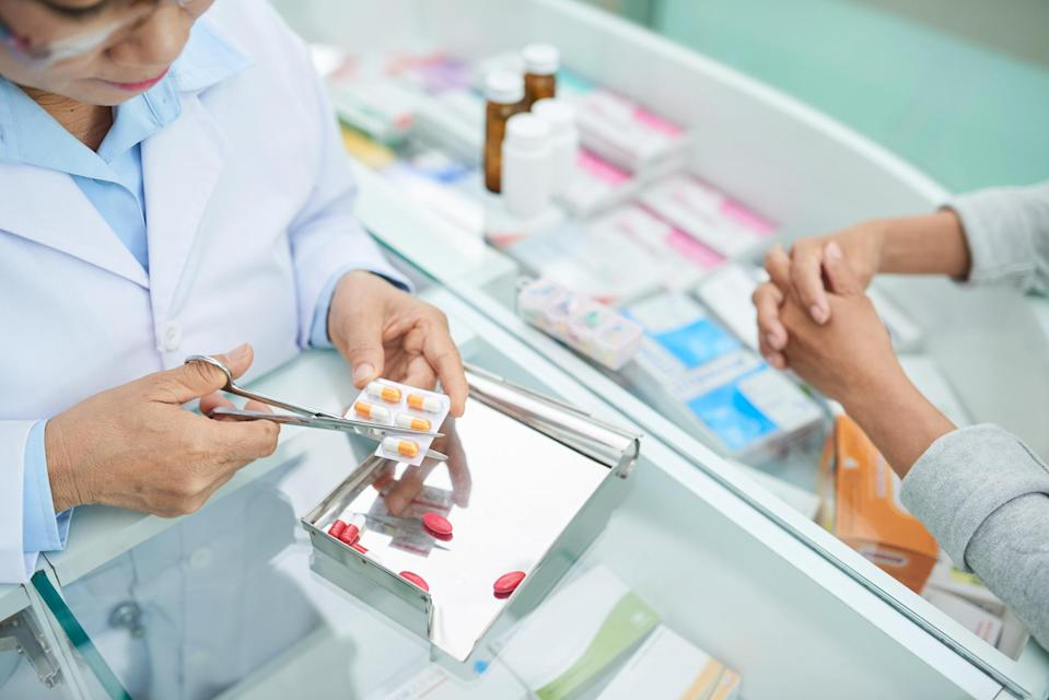 Pharmacists cutting blister package of tablets for customer