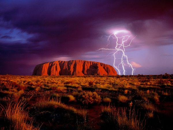 Lightning flashes over Ayers Rock, a landmark red sandstone monolith that draws tourists to Australia's center. Uluru-Kata Tjuta National Park houses the rock, called Uluru by Aborigines, the continent's original inhabitants.
