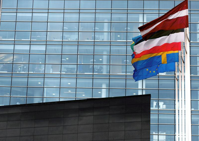 FILE PHOTO: Flags flutter next to the Swedbank Latvian head office in Riga
